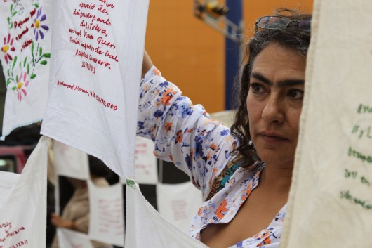 Mother of a disappeaered child peers out from handkerchiefs embroidered with details of missing Mexicans woven together.