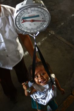 Chronic childhood malnutrition in Guatemala: Two year old Arazeli is weighed. At just 16lb, she is dangerously underweight for her age.