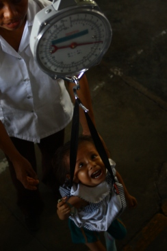 Two year old Arazeli is weighed. At just 16lb, she is dangerously underweight for her age.